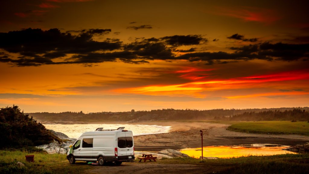 White van parked on a beach with a sunset ahead