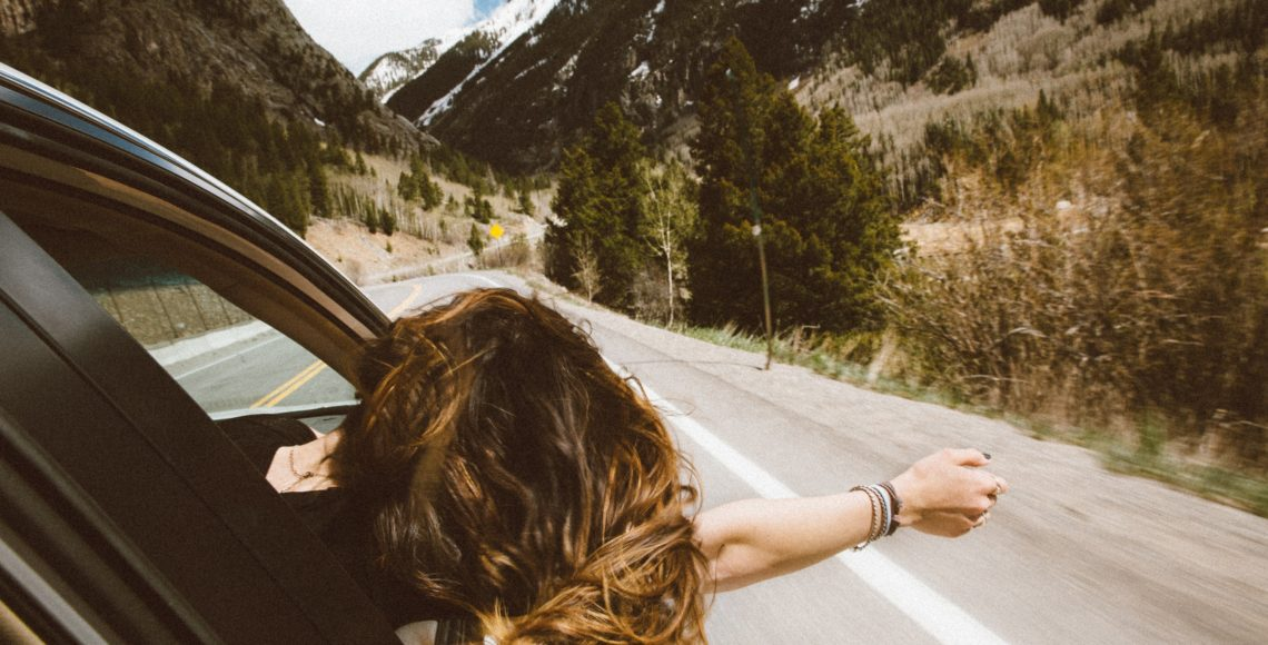 Woman hanging out a car with mountains and the sky ahead of her