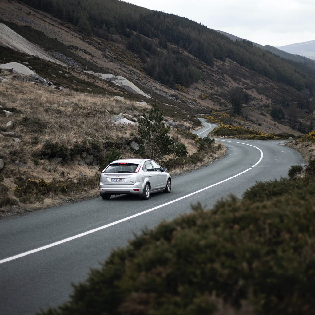 Silver car on a winding mountain road