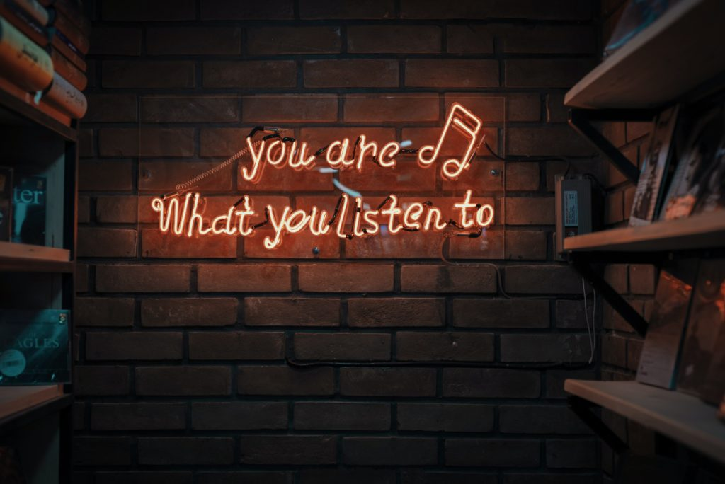 """Neon text on a wall saying """"you are what you listen to"""""""