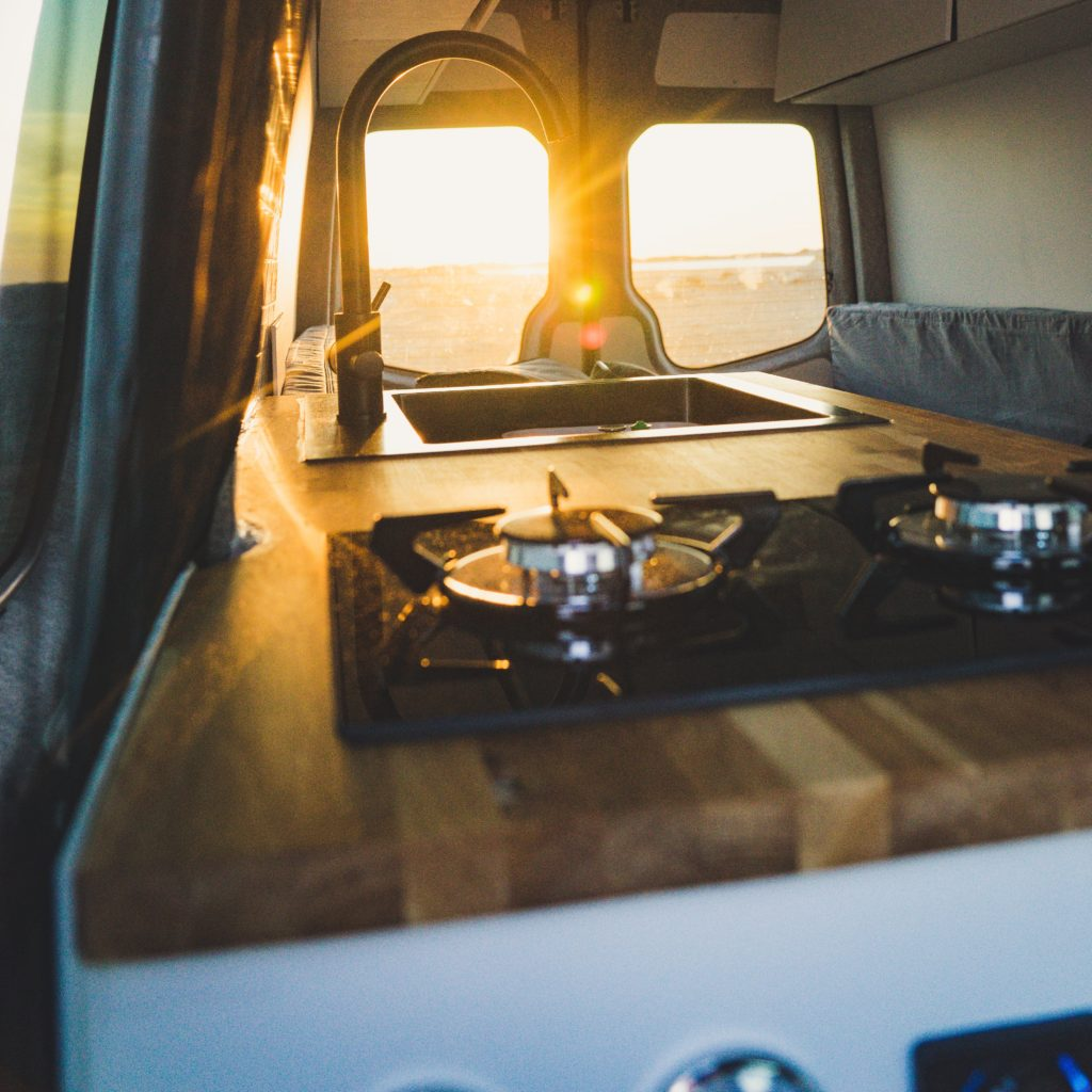 Campervan kitchen with a sunset out the window