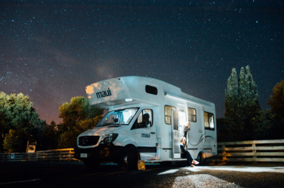 White Motorhome in front of a starry night sky
